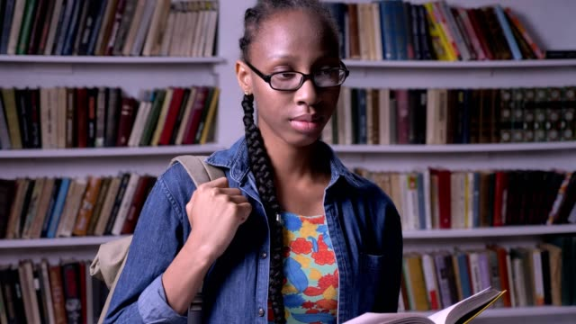 Young-beautiful-african-american-woman-in-glasses-reading-book-in-library-and-looking-at-camera-happy-smiling-bookshelves-background