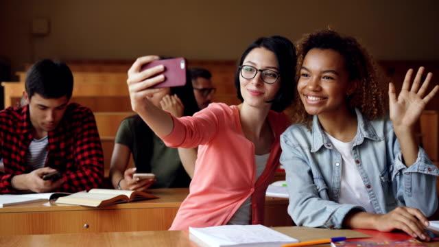 Chicas-alegres-estudiantes-toman-selfie-con-smartphone-sentados-en-mesas-en-el-colegio-las-mujeres-se-plantean-haciendo-gestos-con-las-manos-y-abrazarse-Amigos-y-el-concepto-de-tecnología-