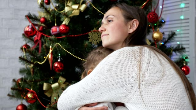 Cute-little-girl-having-fun-and-kissing-her-mom-next-to-Christmas-tree
