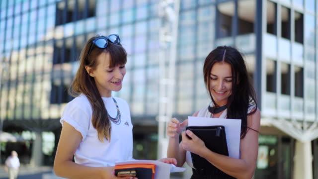 Equipo-de-negocios-creativo-joven-Dos-atractivos-femeninos-corredores-financieros-están-trabajando-juntos-en-una-estadística-sobre-el-papel-junto-a-la-oficina-de-negocios