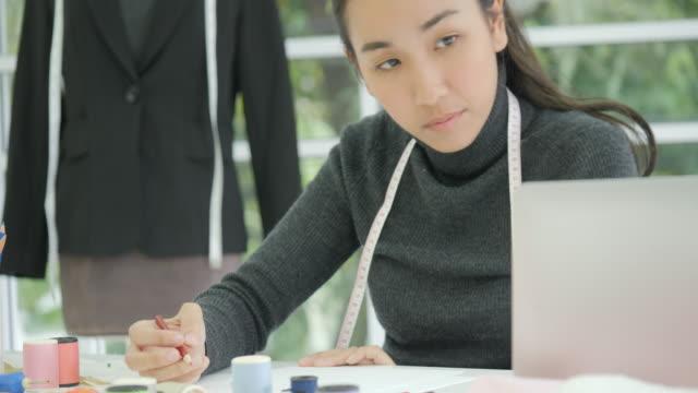 Hermosa-mujer-asiática-moda-diseñador-sentado-en-su-escritorio-mirando-bocetos-en-un-ordenador-portátil-en-estudio-tomando-notas
