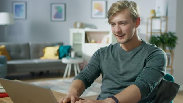 Guapo-sonriente-joven-usando-el-portátil-mientras-está-sentado-en-el-escritorio-de-su-acogedora-sala-de-estar-