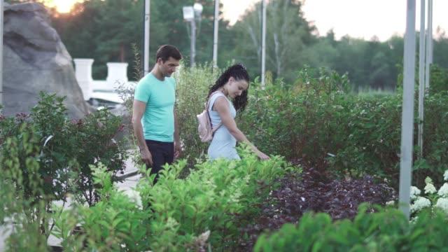 Mujer-y-hombre-adulto-caminan-en-el-jardín-y-hablar