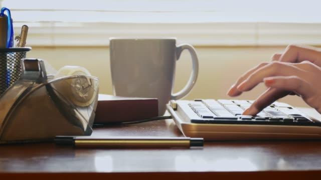 Tiro-de-carro-de-la-mujer-que-trabaja-en-casa-escribiendo-en-una-computadora-de-oficina