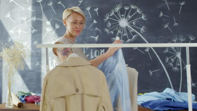 Female-Fashion-Designer-Hanging-Clothes-on-Rail