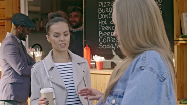Smiling-woman-talking-to-her-friend-near-coffee-shop