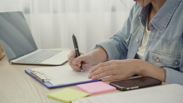 Empresario-joven-asiático-inteligente-hermosa-mujer-empresario-de-PYME-control-de-producto-en-stock-y-escribe-en-el-portapapeles-trabajando-en-casa-Pequeño-empresario-en-concepto-de-la-oficina-en-casa-