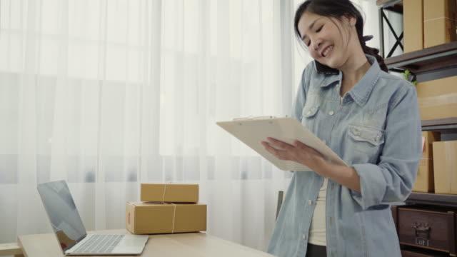 Smart-asiático-mujer-empresario-de-PYME-en-línea-mediante-llamada-telefónica-reciben-de-producto-control-de-cliente-en-la-acción-y-escribir-en-el-portapapeles-trabajo-en-casa-Pequeño-empresario-en-concepto-de-la-oficina-en-casa-