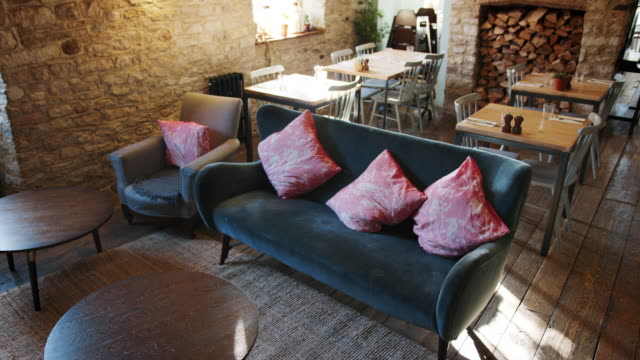 Empty-lounge-dining-space-and-bar-in-a-gastro-pub-in-daylight-with-feature-stone-walls-and-old-wooden-floorboards-handheld-elevated-view