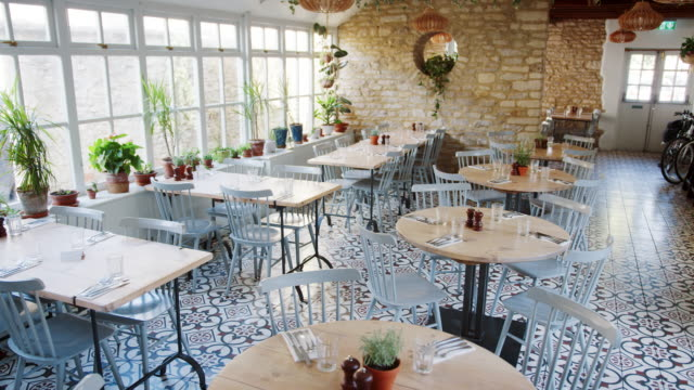 Round-tables-and-duck-egg-blue-chairs-in-an-empty-restaurant-with-patterned-floor-tiles-and-houseplants-growing-on-the-window-sill