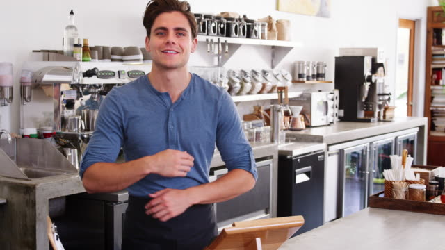 Young-male-coffee-shop-owner-crossing-arms-behind-counter