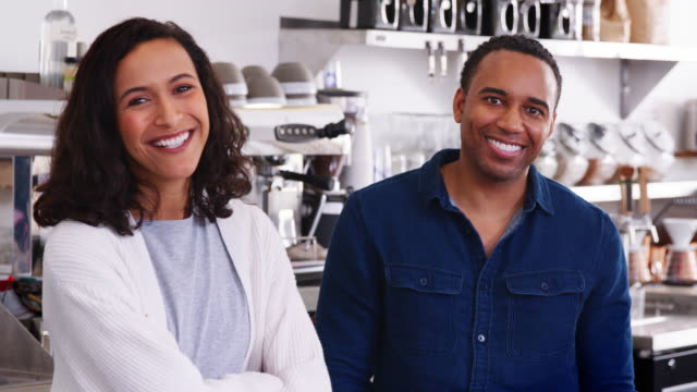 Mixed-race-couple-behind-the-counter-at-their-coffee-shop