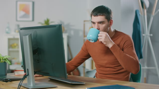 Portrait-of-Handsome-Confident-Man-Working-on-a-Personal-Computer-from-Home-In-Cozy-Bright-Living-Room-Man-Browses-Through-Internet-