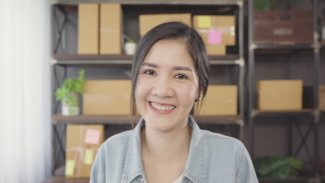 Business-woman-feeling-happy-smiling-and-looking-to-camera-while-working-in-her-office-at-home-Beautiful-Asian-young-entrepreneur-owner-of-SME-with-small-business-owner-at-home-office-concept-