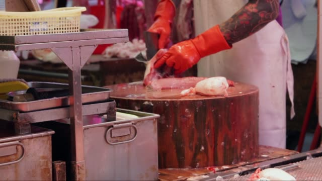 butcher-at-work-slicing-and-packaging-fish-on-a-chopping-block-at-a-meat-market