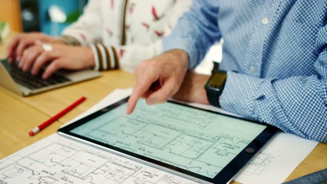 Arquitectos-trabajando-en-planes-de-casa-en-su-estudio