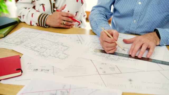 Architekten-zeichnen-und-diskutieren-Hauspläne-In-ihrem-Studio