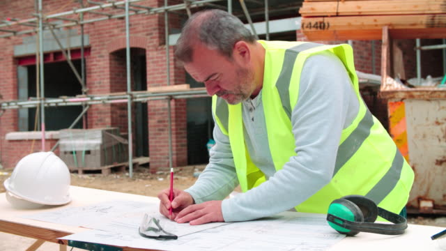 Construction-Worker-Checking-Plans-On-Building-Site