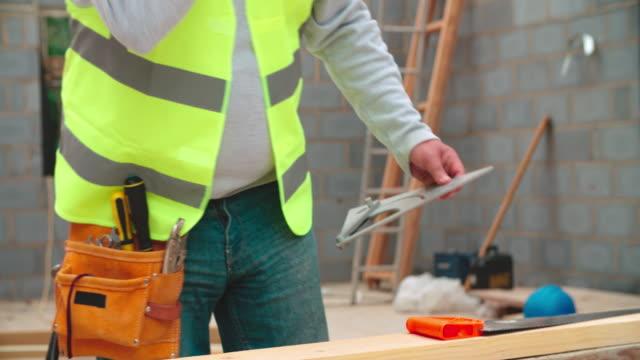 Primer-plano-de-carpintero-medición-de-madera-y-corte-en-el-emplazamiento