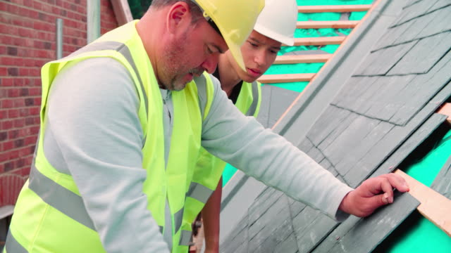 Construction-Worker-With-Apprentice-Laying-Slate-Tiles