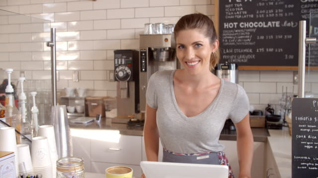 Woman-behind-the-counter-of-a-coffee-shop-crosses-arms
