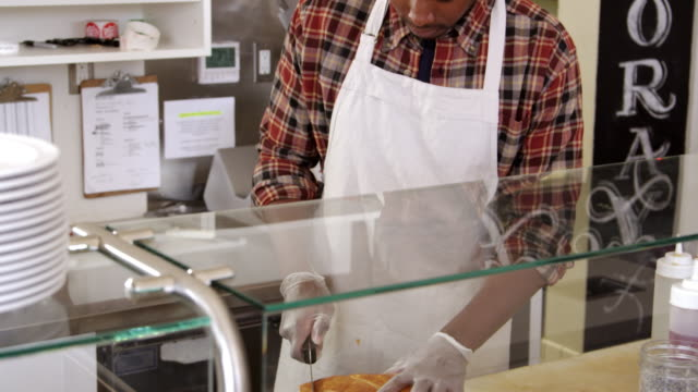 Man-slicing-bread-behind-the-counter-of-a-sandwich-bar-shot-on-R3D