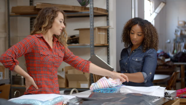 Women-in-post-room-preparing-clothes-orders-for-dispatch