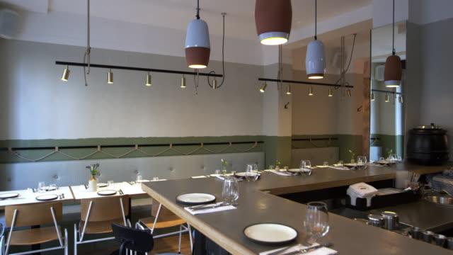 Tiro-de-cámara-deslizante-de-mesas-vacías-y-bar-en-un-restaurante