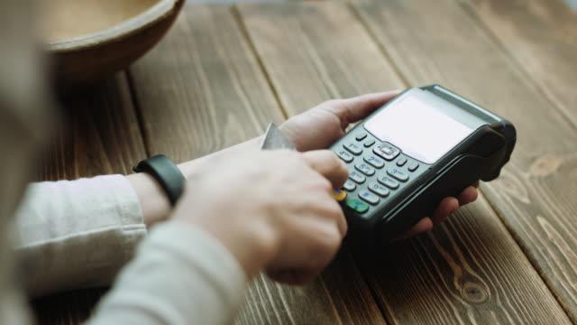 Woman-swiping-credit-card-through-credit-card-reader