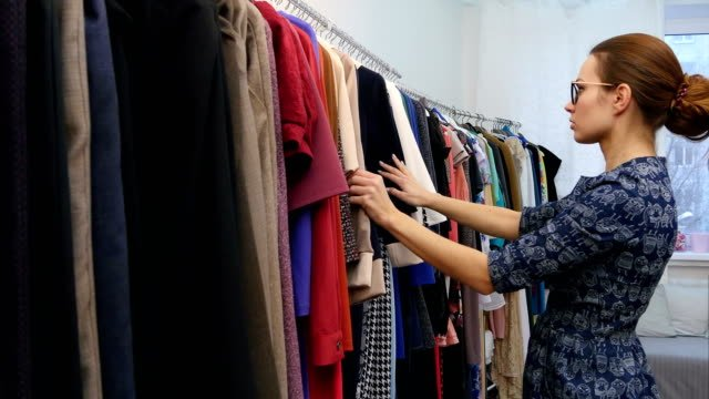 Small-business-owner-in-clothes-shop-checking-collection