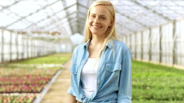 En-un-día-soleado-hermoso-jardinero-rubia-está-sonriendo-en-un-invernadero-lleno-de-flores-coloridas-