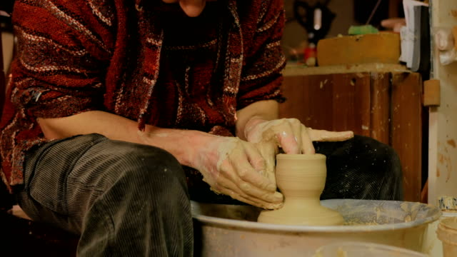 Professional-male-potter-working-in-workshop