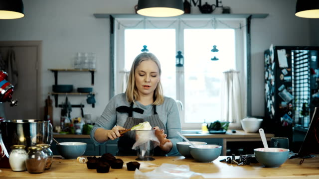 Young-beautiful-woman-standing-on-the-kitchen-and-cooking-cupcakes-Blonde-female-puts-the-cream-in-pastry-bag