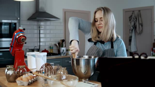 Junge-schöne-Frau-Mischen-der-Zutaten-in-einer-Schüssel-Teig-zum-Backen-vorbereiten-Blonde-Frau-in-der-Küche