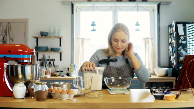 Young-blonde-woman-using-the-kitchen-scales-to-weighing-the-flour-Beautiful-female-baking-the-cupcakes-on-the-kitchen