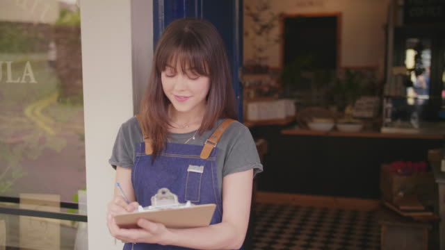 Beautiful-Young-Deli-Owner-Writing-In-Clipboard-Outside-Store