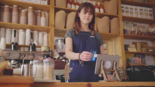 Cajero-de-tienda-Deli-mujer-birlar-la-tarjeta-en-el-lector-de-la-tableta-Digital