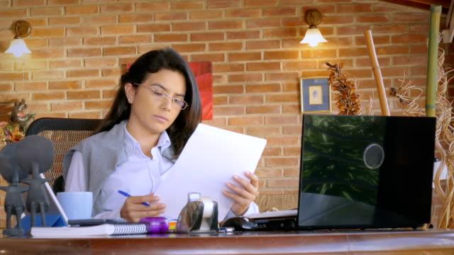 Tiro-de-carro-de-mujer-joven-hispana-trabajando-en-casa-oficina-y-lectura-documments-trabajando-en-ordenador-portátil-