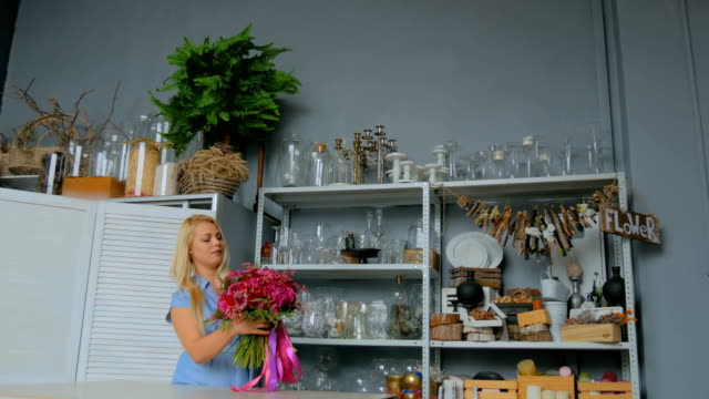 Professional-florist-holding-and-checking-bouquet-at-studio