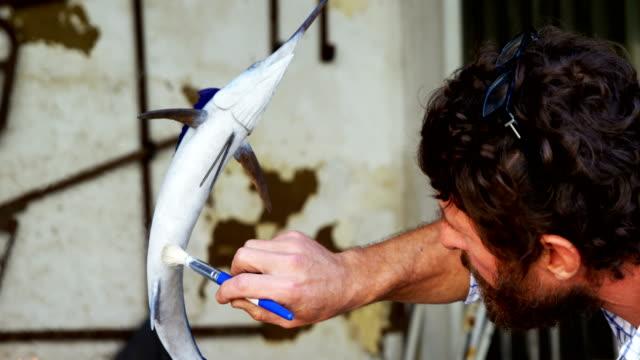 Craftsman-polishing-fish-sculpture-4k
