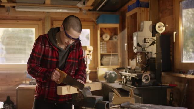 Joven-valiente-cortar-madera-en-el-taller-hacia-los-lados