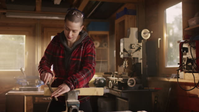 Short-haired-woman-working-with-a-wood-file-and-looking-strong-into-the-camera