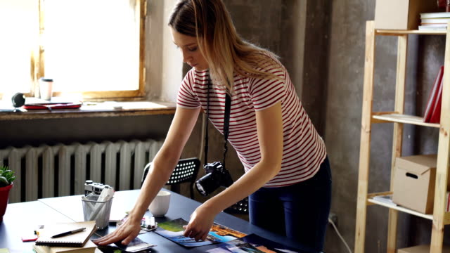 Young-female-photographer-is-making-flat-lay-from-colorful-photos-on-table-and-shooting-them-with-camera-She-is-displaying-pictures-near-color-palette-and-markers-on-desk-