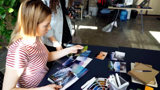 Kreative-Kollegen-Bilder-Inverkehrbringen-Tabelle-und-schießen-flach-legen-während-des-Gesprächs-über-Design-Projekt-Draufsicht-der-moderner-Tisch-mit-Illustrationen-