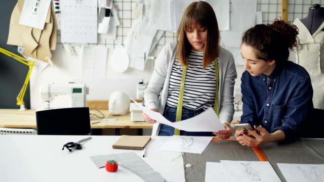 Mujeres-jóvenes-que-trabajan-en-la-industria-del-diseño-son-comparando-dibujos-y-hablar-de-ellos-mientras-trabajaba-en-la-sastrería-moderna-Concepto-de-trabajo-productivo-en-equipo-