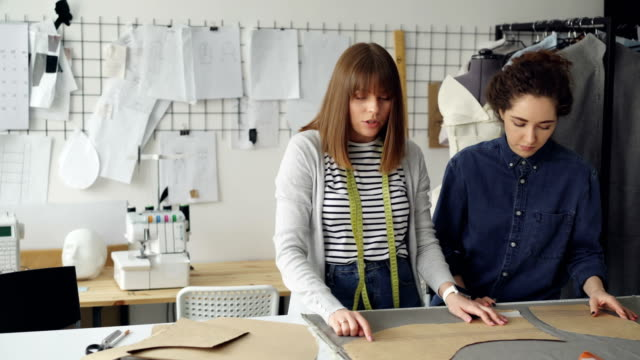 Team-of-creative-designers-is-working-with-clothing-patterns-and-fabric-in-tailor-s-shop-Young-women-are-concentrated-on-measuring-Sewing-items-and-tools-in-background-