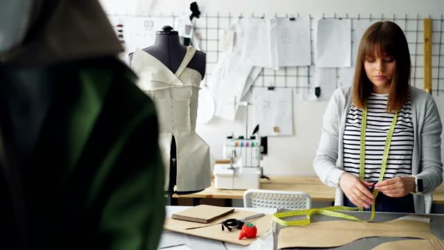 Sastre-mujer-atractiva-es-medición-de-patrones-de-ropa-con-cinta-métrica-en-su-luz-sastrería-Trabajo-diario-en-concepto-de-la-industria-de-fabricación-de-ropa-