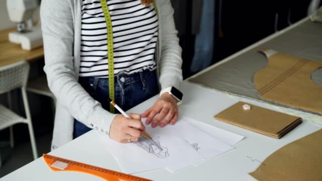 Incline-para-arriba-tiro-de-diseñador-de-ropa-creativa-se-concentró-en-dibujo-dibujo-de-ropa-de-las-mujeres-en-papel-con-lápiz-Creando-el-concepto-de-ropa-de-moda-