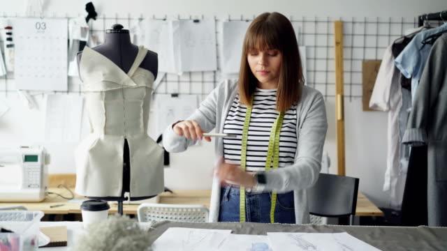 Hermosa-mujer-diseñadora-de-moda-es-tomar-fotos-de-bocetos-de-mentira-en-la-tabla-Ella-está-haciendo-pone-plano-creativo-Su-estudio-es-claro-y-completo-de-equipos-herramientas-y-artículos-de-costura-