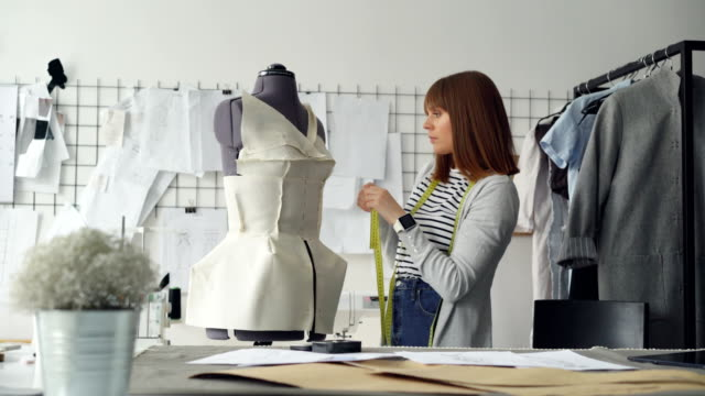 Young-attractive-seamstress-is-measuring-tailor-s-dummy-with-tape-to-make-new-garment-with-these-measurements-Busy-day-in-clothing-workshop-concept-